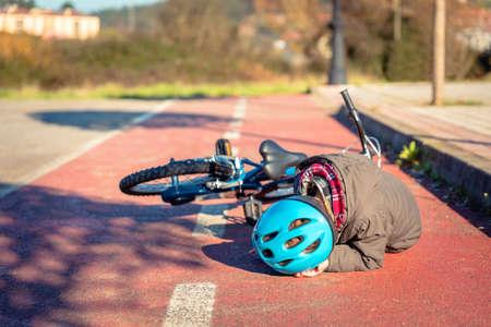 Menino no chão rua tocar a cabeça protegida com um capacete após cair de sua bicicleta