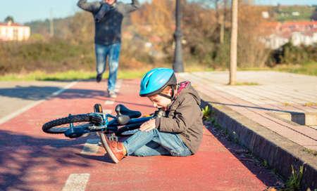 Boy az utcán földön egy térdsérülés sikoltozás után leesik a kerékpárját Stock fotó