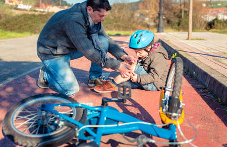 Father putting a plaster band over knee injury to his son after falling off to the bicycle