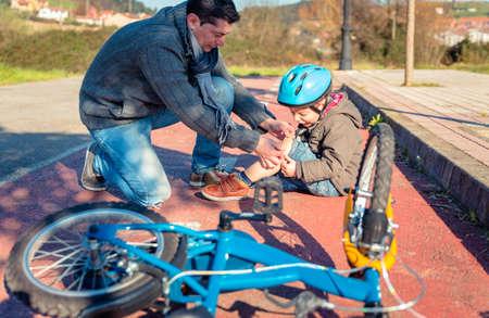 de rodillas: Padre poniendo una venda de yeso sobre la lesi�n de rodilla a su hijo despu�s de caerse de la bicicleta Foto de archivo