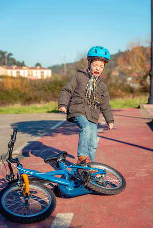 behave: Naughty boy screaming and kicking his bike on the street ground after falling off Stock Photo