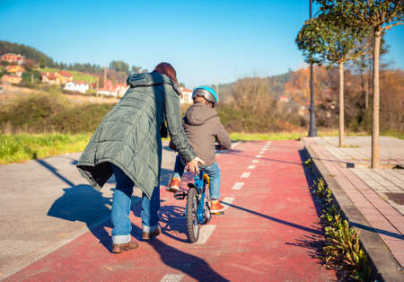 cycleway: Back view of mother teaching her son to ride a bicycles in the city on a sunny winter day.  Family leisure outdoors concept.