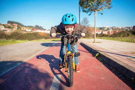 defiant: Portrait of naughty boy with defiant gesture over his bike ready to run on a cycleway Stock Photo
