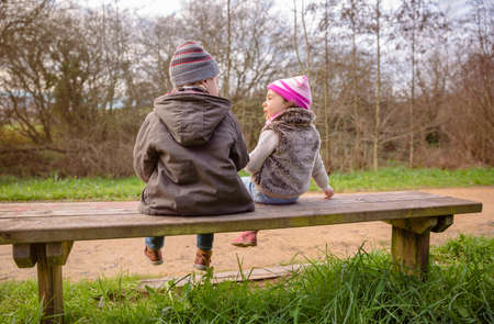 Back view of happy cute boy and little girl talking and playing sitting on a wooden bench in the park photo