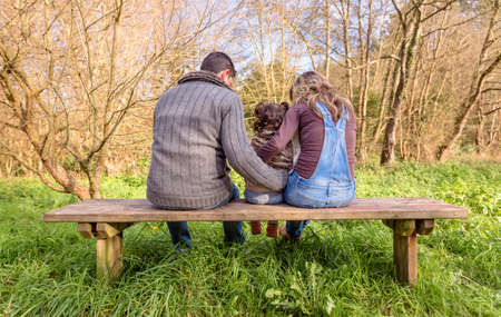 Back view of man and woman hugging to a little girl sitting on the center of a wooden bench in the park. Family leisure outdoors concept. photo