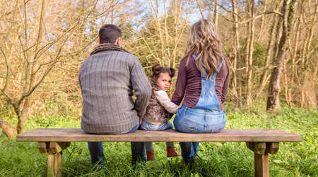 back to camera: Back view of angry little girl looking to the camera between of man and woman sitting on a wooden bench in the park