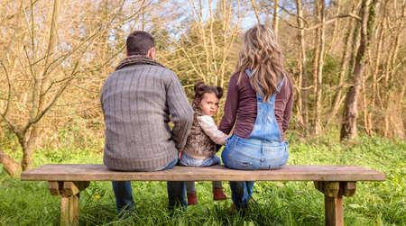Vue arrière de colère petite fille à la recherche de la caméra entre l'homme et la femme assis sur un banc de bois dans le parc