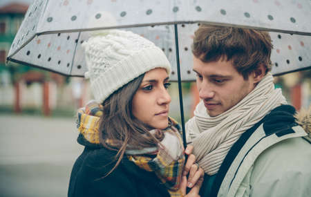 rainy day: Portrait of young beautiful couple in love looking under the umbrella in an autumn rainy day. Love and couple relationships concept. Stock Photo