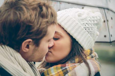 young couple kiss: Detalle de la joven y bella pareja bes�ndose bajo el paraguas en un lluvioso d�a de oto�o. El amor y las relaciones de pareja concepto.