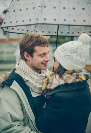 couple winter: Portrait of young beautiful couple embracing under the umbrella in an autumn rainy day. Love and couple relationships concept.
