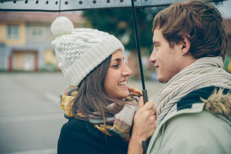 couple winter: Closeup of young beautiful couple embracing and laughing under the umbrella in an autumn rainy day. Love and couple relationships concept.