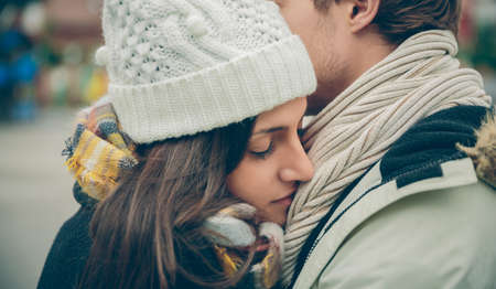 eye closed: Closeup of young beautiful couple with hat and scarf embracing in a cold autumn day. Love and couple relationships concept.
