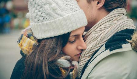 uomo sotto la pioggia: Primo piano di giovane bella coppia con cappello e sciarpa avvolgente in un giorno di autunno freddo. Amore e relazioni di coppia concetto.