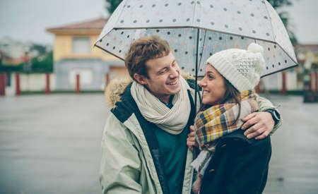 Portrait of young beautiful couple embracing and laughing under the umbrella in an autumn rainy day. Love and couple relationships concept.