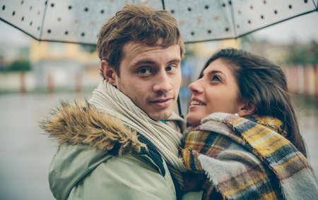 uomo sotto la pioggia: Primo piano di giovane coppia felice che abbraccia sotto l'ombrello in un giorno di autunno piovoso. Amore e relazioni di coppia concetto. Archivio Fotografico