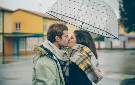 love in rain: Portrait of young beautiful couple kissing under the umbrella in an autumn rainy day. Love and couple relationships concept. Stock Photo