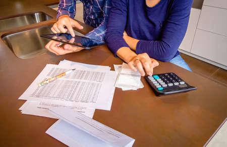 디지털 태블릿 및 계산기 집에서 자신의 은행 계좌를 검토하는 젊은 부부 확대 사진. 금융 가족 개념입니다.