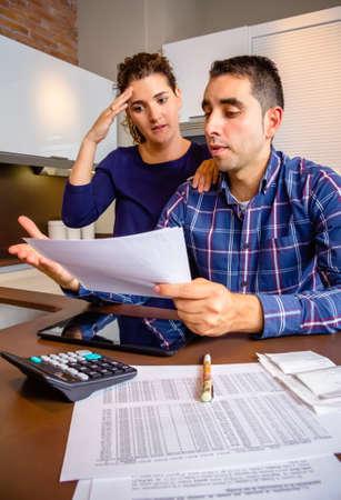 problemas familiares: Pareja de j�venes desempleados con muchas deudas revisar sus cuentas bancarias. Concepto financiero de los problemas familiares. Foto de archivo