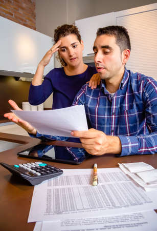 Unemployed young couple with many debts reviewing their bank accounts. Financial family problems concept. photo