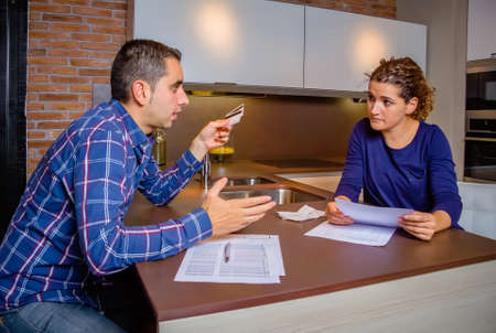 family problems: Angry young couple arguing at home by their many credit card debts. Financial family problems concept.