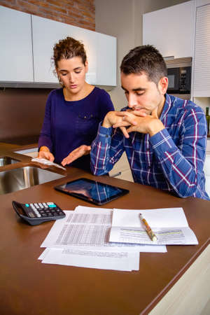 Unemployed young couple with many debts reviewing their bills. Financial family problems concept. Stockfoto