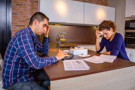 Desperate and unemployed young couple reviewing their credit card debts. Financial family problems concept. Archivio Fotografico