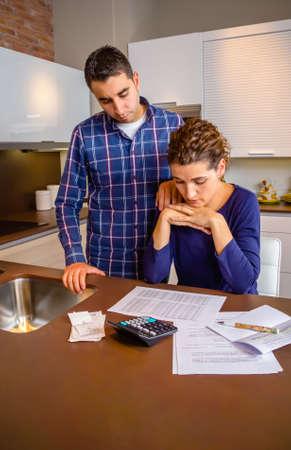 Verzweifelte junge Paar mit vielen Schulden Überprüfung ihrer Rechnungen. Finanzielle Probleme in der Familie Konzept. Standard-Bild - 38271265
