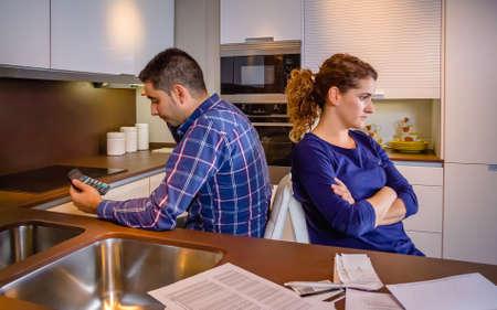 problemas familiares: Pareja joven enojado sentados espalda con espalda después de una pelea dura por sus muchas deudas en casa. Concepto financiero de los problemas familiares.