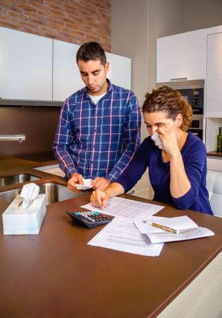 problemas familiares: Joven marido desempleado revisar los proyectos de ley y su esposa desesperada llorando por sus deudas. Concepto financiero de los problemas familiares.