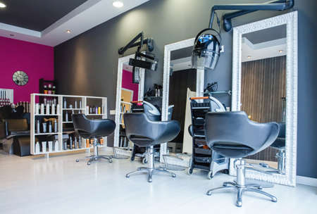 Interior of empty modern hair and beauty salon decorated in gray and fuchsia colors