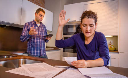 family problems: Angry young couple arguing by their many debts at home. Financial family problems concept.