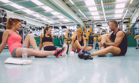 Group of friends talking sitting on the floor of a fitness center after hard training day Archivio Fotografico