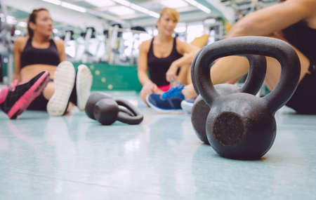 Closeup of black iron kettlebell and people group sitting on the floor of a fitness center in the background Stock Photo
