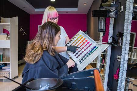 tinte cabello: Joven y bella mujer mirando con una paleta de peluquería tintes de cabello para cambiar su color de pelo