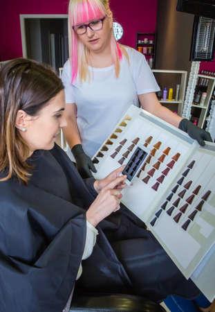 tinte de cabello: Mujer joven hermosa con peluquer�a toma una foto con su tel�fono inteligente a la paleta de tinte para el cabello