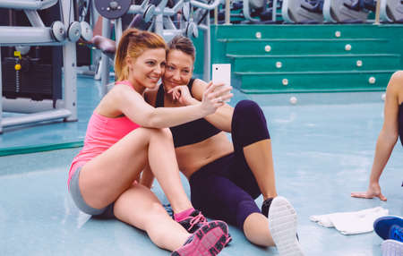 taking a break: Young beautiful women friends taking a selfie with smartphone sitting on the floor of a fitness center after hard training day
