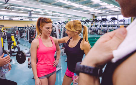 aide � la personne: Personal trainer encourageant � triste jeune femme apr�s une journ�e de dur entra�nement dans le gymnase