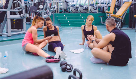 personal trainer: Young beautiful women looking the smartphone while a couple friends talking sitting on the floor of fitness center