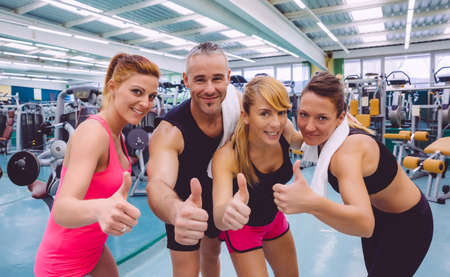 woman thumbs up: Group of friends with thumbs up smiling on a fitness center after hard training day Stock Photo