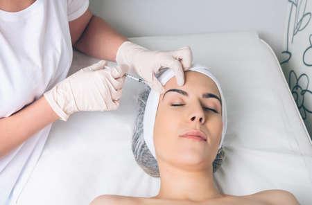 inyecci�n: Mujer bonita joven que consigue la inyecci�n de cosm�ticos en la cara como una parte del tratamiento de la cl�nica. Medicina, salud y el concepto de belleza. Foto de archivo