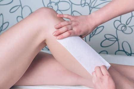 depilacion con cera: Primer de las manos haciendo la depilaci�n est�tica de hermosas piernas de la mujer con la tira de cera en un sal�n de belleza Foto de archivo