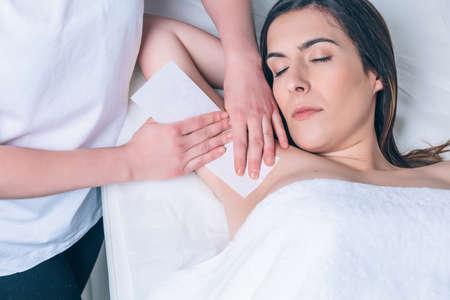 depilacion con cera: Manos de estética hacen axila depilación a la mujer hermosa con la tira de cera en un salón de belleza