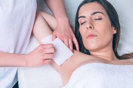 Mãos do Beautician que faz a depilação das axilas de mulher bonita com tiras de cera em um salão de beleza
