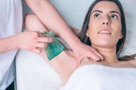 Kosmetička ruce dělá depilace podpaží na krásné ženy s horkým voskem v salonu krásy Reklamní fotografie