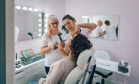 Portrait of make-up artist teaching to make good makeup in a beauty center Standard-Bild