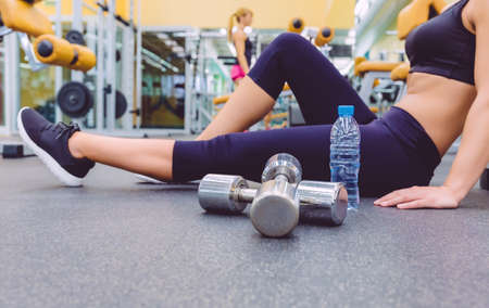 Closeup of sporty woman resting sitting on the floor of fitness center and female friend doing exercises with dumbbells in the background. Selective focus on a dumbbles.
