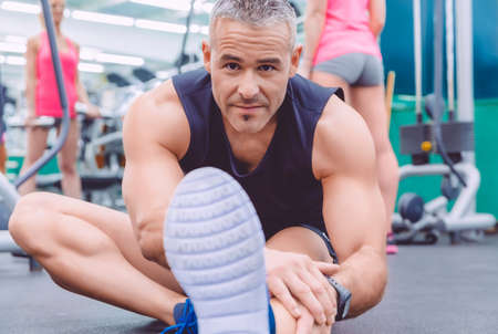 Portrait of handsome man stretching in a fitness center and beautiful woman doing exercises with dumbbells in the background photo