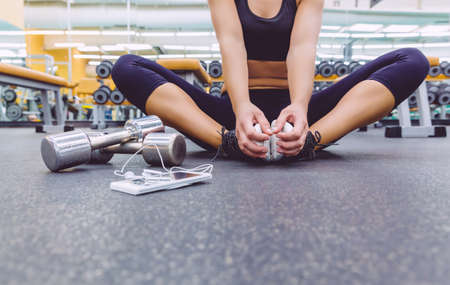 Closeup of sporty woman sitting on the floor of fitness center with dumbbells and smartphone with earphones in the foreground