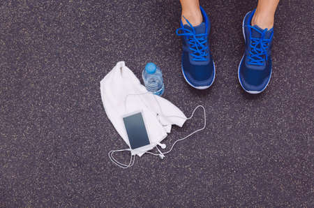 gym floor: Top view of man legs with sneakers, towel, water bottle and smartphone with earphones over a dark gym floor background