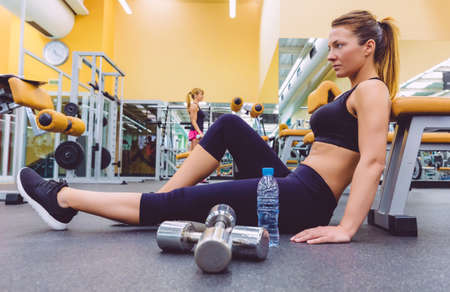 Beautiful sporty woman resting sitting on the floor of fitness center and female friend doing exercises with dumbbells in the background photo